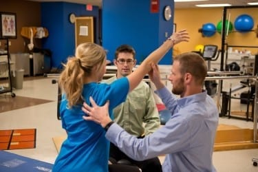 Physical therapists lead a patient through shoulder exercises