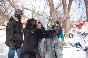 Nisha Fahey embraces her friend, Rhonda. HCO members visit some of the city's homeless individuals every Sunday morning.