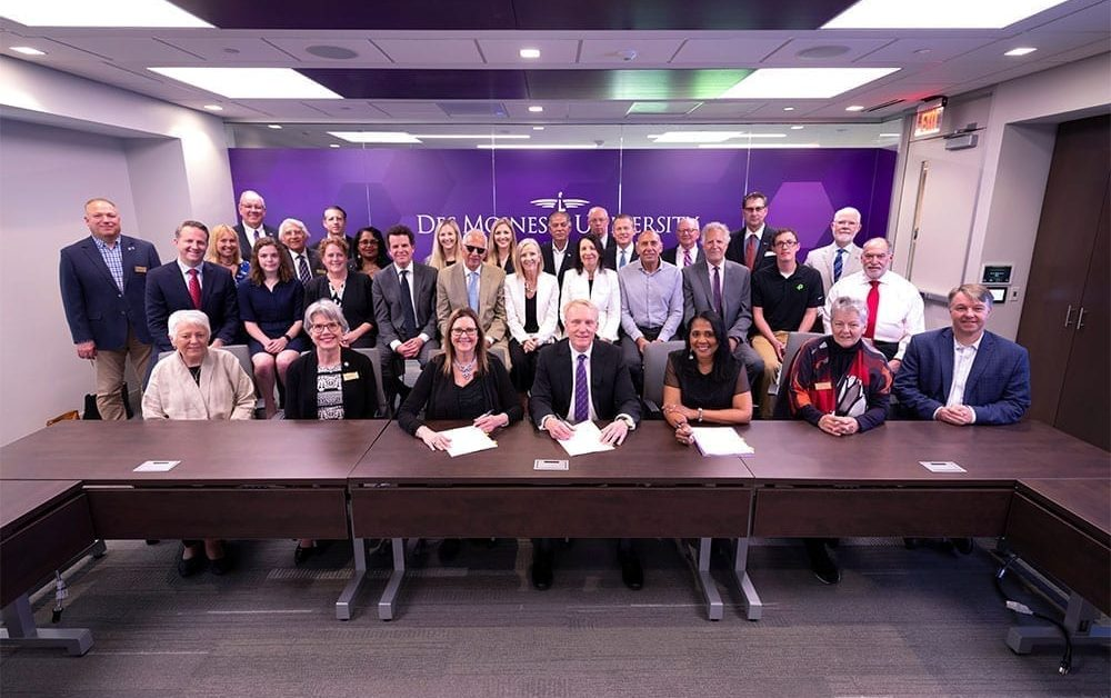 DMU Board Chair Michael Witte and University President Angela Walker Franklin - seated, fourth and third from right, respectively - are joined by DMU trustees, members of the McKinney family and West Des Moines leaders for the signing of the purchase of property for a new campus.