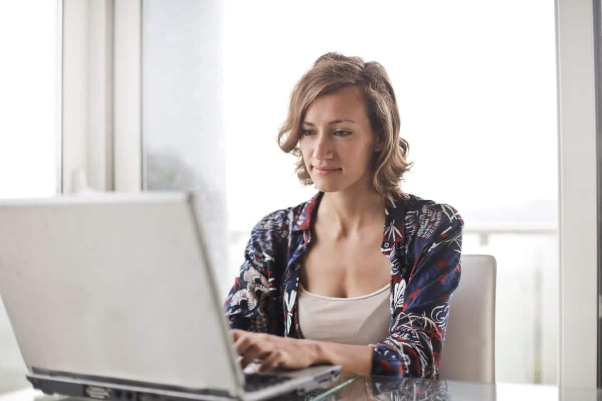 woman-in-blue-floral-top-sitting-while-using-laptop-806835