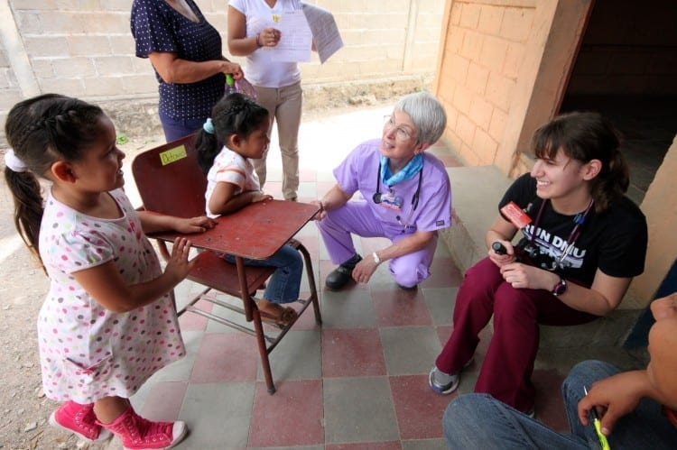 Dr. Rebecca Shaw and Molly Olson, D.O.'16, M.P.H.'16, interact with young patients in a Honduran clinic.