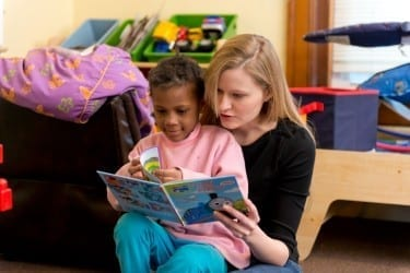 Kelsey Randel reads with a friend at New Directions Shelter.