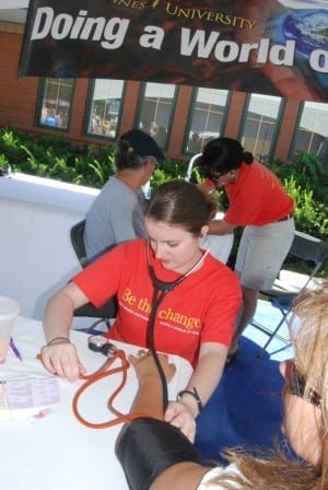 At the Iowa State fair a DMU student tests someone's blood pressure